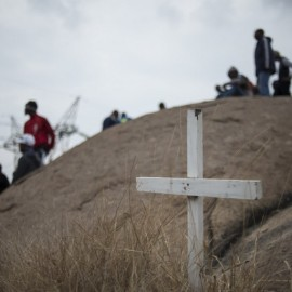 This picture taken on August 16, 2014 shows a white cross as people gather in Marikana, next to the hill where two years ago miners where gunned down by the South African police during a violent wave of strikes. Thousands of South African platinum mineworkers on August 16 gathered at Marikana to commemorate the second anniversary of the killing of 34 of their colleagues by police during a strike. AFP PHOTO/MUJAHID SAFODIEN